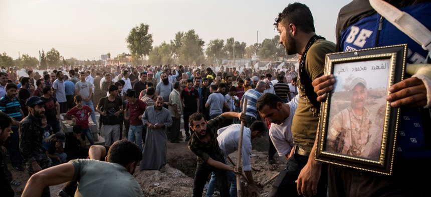 Syrians bury Syrian Democratic Forces fighters killed fighting Turkish advance in the Syrian town of Qamishli, Saturday, Oct. 12, 2019, Turkey's military says it has captured a key Syrian border town Ras al-Ayn under heavy bombardment.
