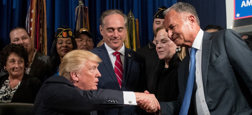 "Donald Trump, left, accompanied by Veterans Affairs Secretary David Shulkin, center, shakes hands with Isaac ""Ike"" Perlmutter, an Israeli-American billionaire, and the CEO of Marvel, right, before signing an executive order in 2017."