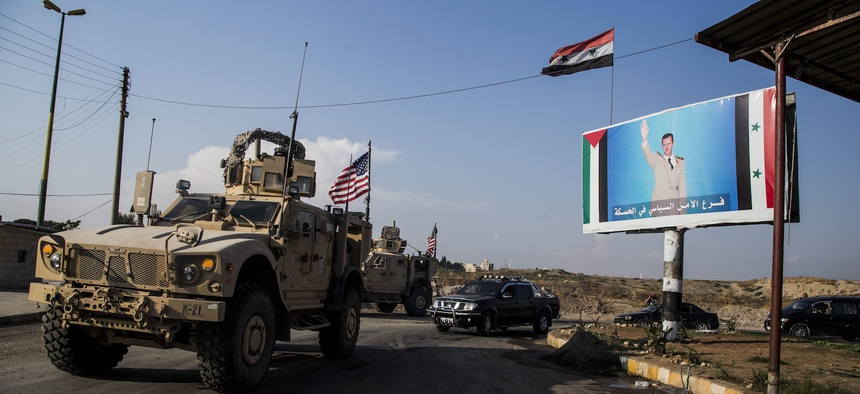 A U.S. military convoy drives through the town of Qamishli, north Syria, by a billboard showing Syrian President Bashar Assad on Saturday, Oct. 26. 2019.
