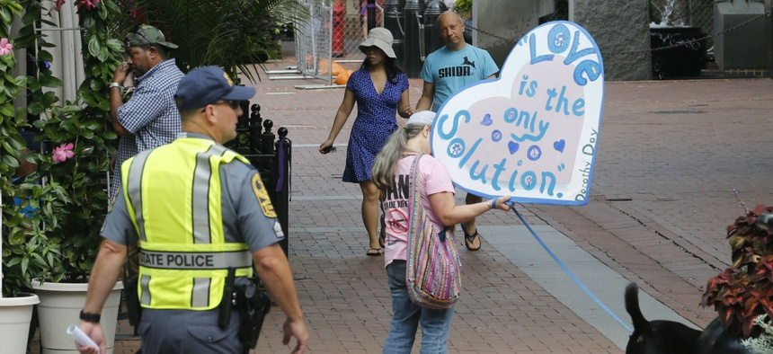 A visitor carries a sign as State Police lock down Charlottesville, Va., in 2018 in anticipation of the one-year anniversary of the Unite the Right rally.