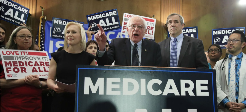 Sen. Bernie Sanders, I-Vt., joined by, Sen . Kirsten Gillibrand, D-N.Y., front left, and Sen. Jeff Merkley, D-Ore., front right, introduces the Medicare for All Act of 2019 on Capitol Hill in April.