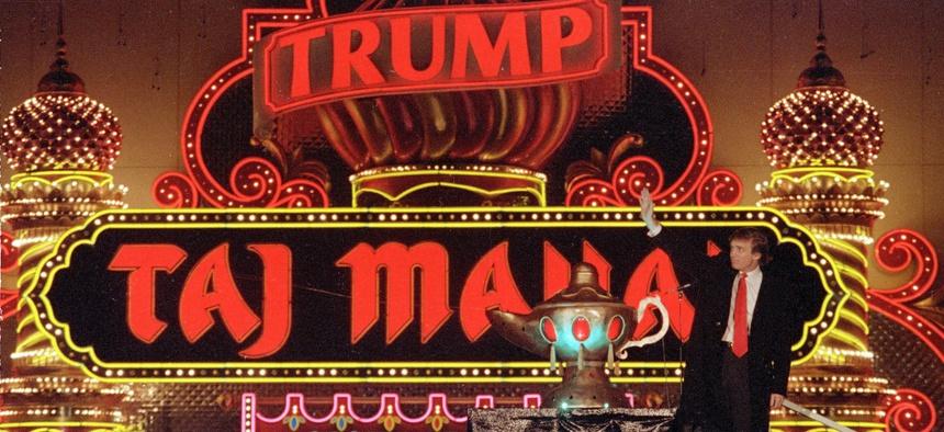 Donald Trump stands next to a genie lamp of his Trump Taj Mahal Casino Resort in 1990.