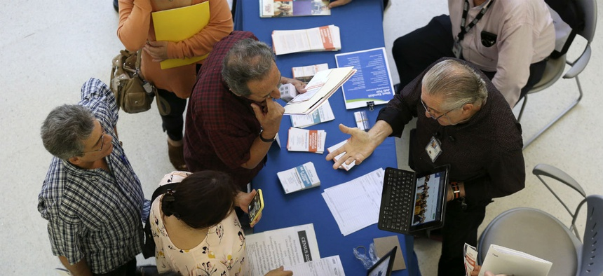 Alex Pereira, of the U.S. Census Bureau, right, talks with job applicants about temporary positions available with the 2020 Census, during a job fair designed for people fifty years or older on Sept. 18 in Miami.