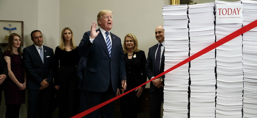 """Let's cut the red tape, let's set free our dreams,"" Trump said as he symbolically cut a ribbon on stacks of paper representing the size of the regulatory code at an event at the White House in December 2017."