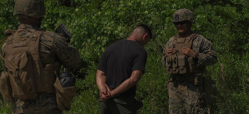 U.S. Marine Corps Lance Cpl. Ulysses Sebastian Brindiz, a military policeman with 2nd Law Enforcement Battalion (LE Bn), II Marine Expeditionary Force, Information Group tactically questions a detainee during an exercise in LZ Phoenix, N.C., May 18, 2019.