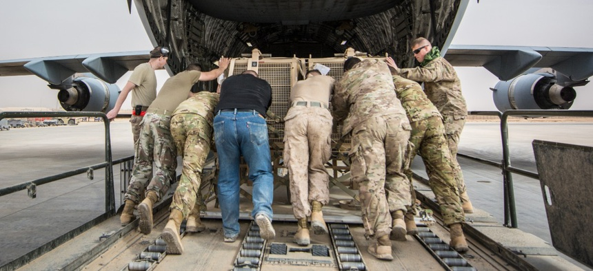 Soldiers, Marines, Airmen and civilian contractors push equipment into the cargo bay of a C-17 Globemaster III, assigned to the 816th Expeditionary Airlift Squadron, at Al Asad Air Base, Iraq Jan. 25, 2018.