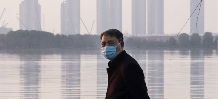 A man wears a face mask as he stands along the waterfront in Wuhan in central China's Hubei Province, which is at the center of the Coronavirus outbreak.
