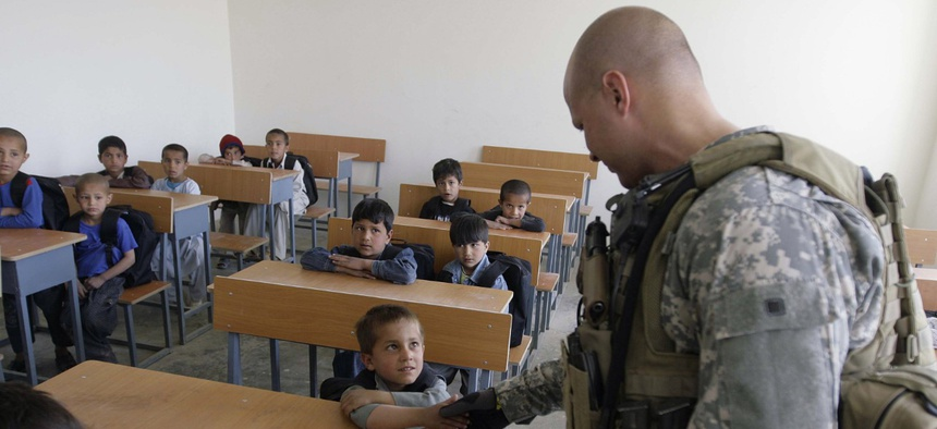 A U.S. soldier of Combined Joint Special Operations Task Force Afghanistan shakes hand with an Afghan boy during the opening of a school in Bagram, north of Kabul, Afghanistan, Monday, March 24, 2008.