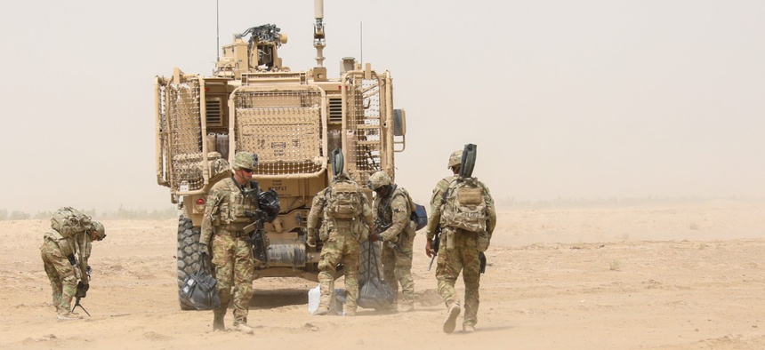 U.S. Army Soldiers from 2nd Infantry Brigade Combat Team, 4th Infantry Division, unload humanitarian aid supplies from a tactical military vehicle in 2018.