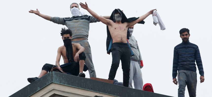Inmates stand on the roof of the San Vittore prison to protest after restrictions that were imposed on family visits to prevent coronavirus transmissions in Milan, Italy, on Monday. The Federal Bureau of Prisons says it is prepared for the coronavirus.