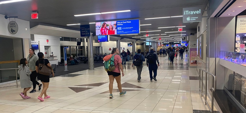 Travelers walk through the Hartsfield-Jackson Atlanta International Airport on Saturday, where flight cancellations and restrictions caused by the coronavirus outbreak left some passengers stranded.