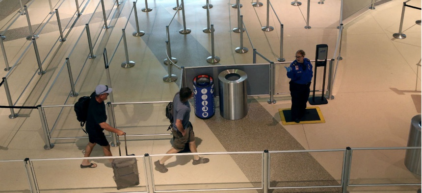 A TSA agent speaks to travelers passing through an empty security queue at Love Field airport in Dallas on March 12.