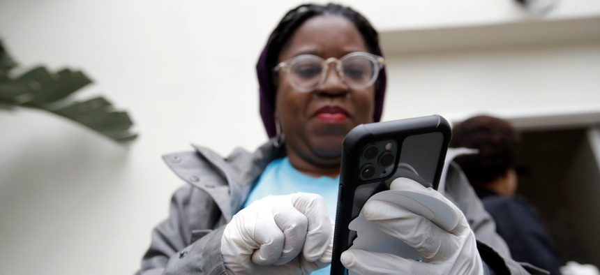 Millie Phaeton wears gloves as she checks her cell phone while volunteering at a food distribution center set up by the Dream Center on Monday in Los Angeles.