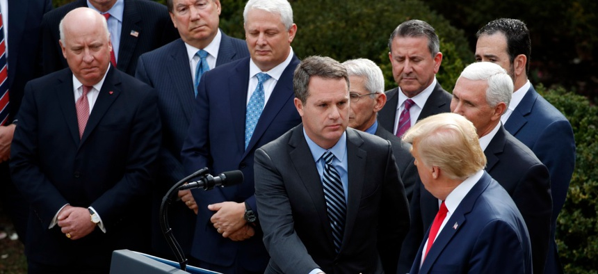 President Donald Trump shakes hands with Walmart CEO Doug McMillon at a White House press conference joining government and corporate officials – but no representatives of workers.
