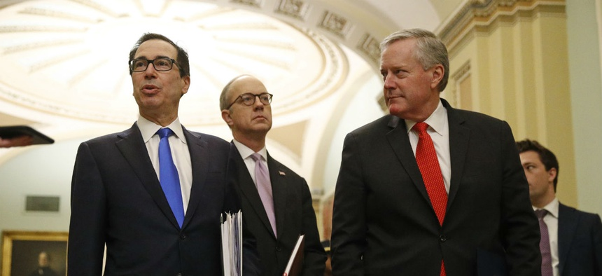 Treasury Secretary Steven Mnuchin, left, accompanied by White House Legislative Affairs Director Eric Ueland and acting White House chief of staff Mark Meadows meet with lawmakers Tuesday to discuss an economic stimulus package in response to coronavirus.