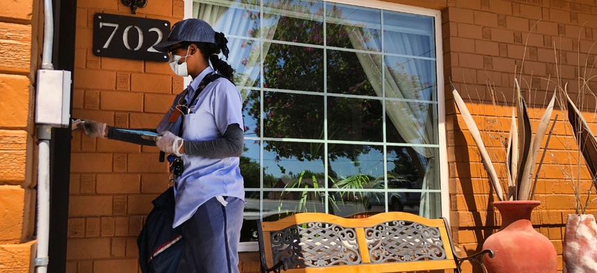 A letter carrier in Phoenix, Arizona, wears a mask and gloves as she delivers mail on Tuesday.