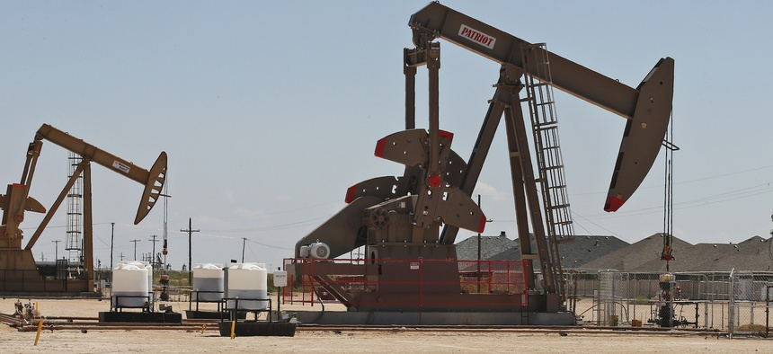 Pump jacks stand next to a housing development in Odessa, Texas in 2019.