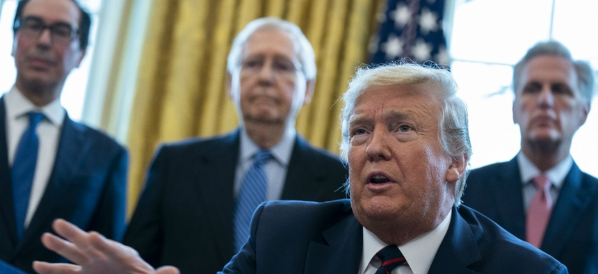 President Trump talks to reporters before signing the coronavirus stimulus relief package in the Oval Office on March 27, as Treasury Secretary Steven Mnuchin, Senate Majority Leader Mitch McConnell and House Minority Leader Kevin McCarty look on.