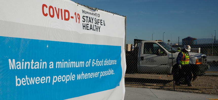 A sign gives guidelines for protection from COVID-19 as construction continues at Allegiant Stadium in Las Vegas on Tuesday.