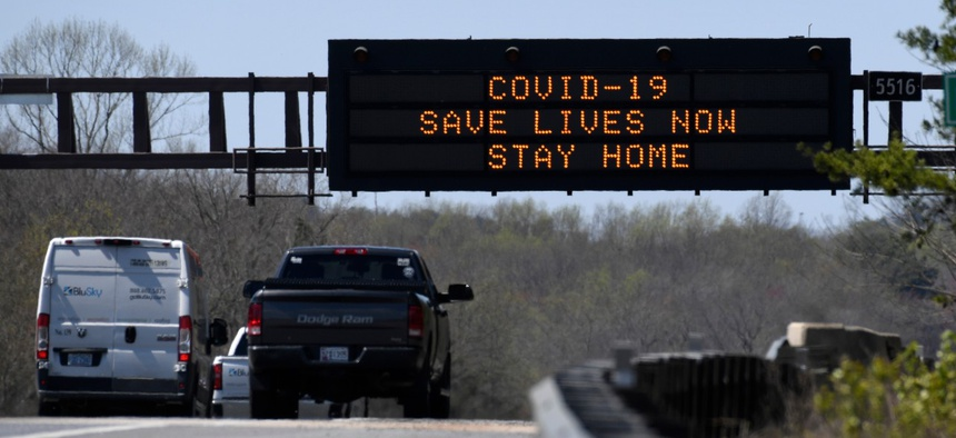 """A sign about the coronavirus is displayed over Route 50 in Davidsonville, Md. Maryland Gov. Larry Hogan issued a """"stay-at-home"""" directive in response to the coronavirus on Monday."""