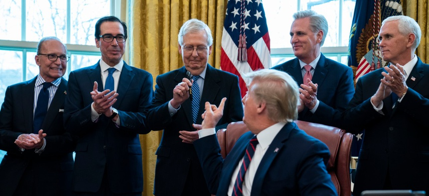 President Donald Trump hands a pen to Senate Majority Leader Mitch McConnell, R-Ky., after signing the coronavirus stimulus relief package March 27.