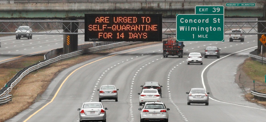 A highway sign urges out of state visitors to self-quarantine for 14 days if they plan on staying in Massachusetts due to the virus outbreak along Route 93 southbound in Wilmington, Mass. on Monday.