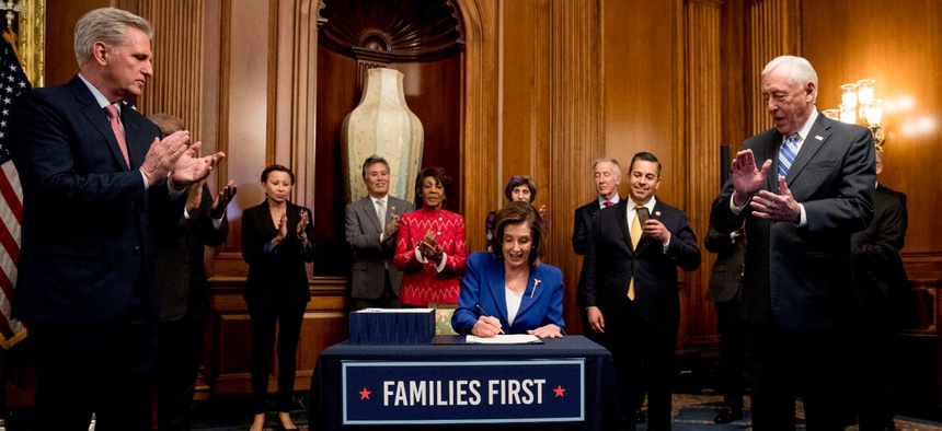 House Speaker Nancy Pelosi of California (center) signs the Coronavirus Aid, Relief and Economic Security Act on March 27.