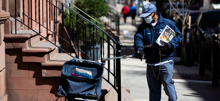 A mail carrier makes a delivery in Philadelphia on April 2.