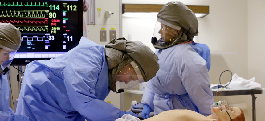 Medical workers wearing PAPR, similar to the ones produced by AirBoss, surround and monitor a simulated patient during a demonstration for media members on their training for working with possible Ebola patients in 2014.