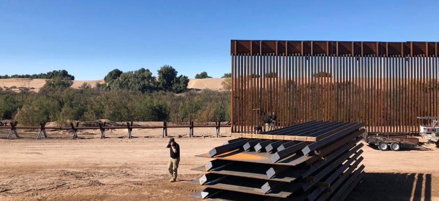 People work on a portion of border wall in Yuma, Ariz., in January. Construction on the wall has not stopped despite the pandemic.