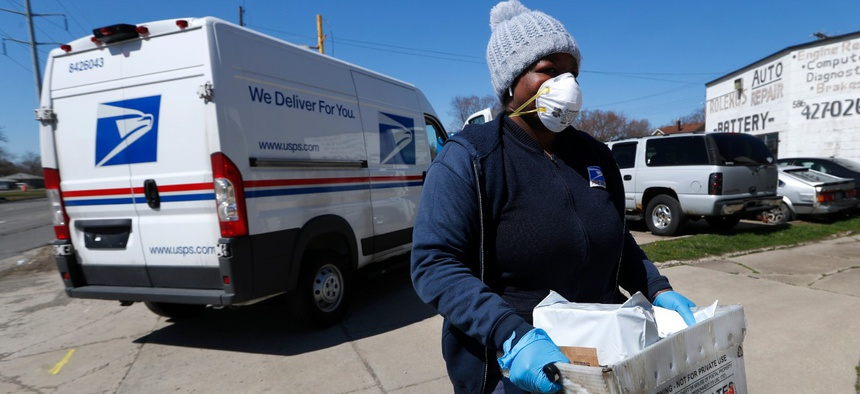 A United States Postal worker makes a delivery with gloves and a mask in Warren, Mich., on April 2.