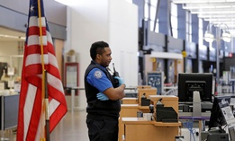 TSA officer C.J. Brooks stands waiting for a passenger to screen in a nearly empty Seattle-Tacoma International Airport on April 15.