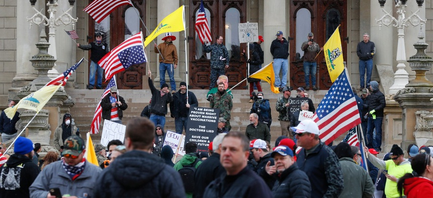 Protesters stand on the steps of the State Capitol in Lansing, Mich., Wednesday, April 15. Flag-waving, honking protesters drove past the Michigan Capitol on Wednesday to show their displeasure with Gov. Gretchen Whitmer.