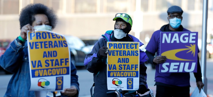 Activists from the American Federation of Government Employees local 424 and the National Association of Government Employees local R3-19 picket during the coronavirus pandemic, outside the Baltimore VA Medical Center, Wednesday, April 22