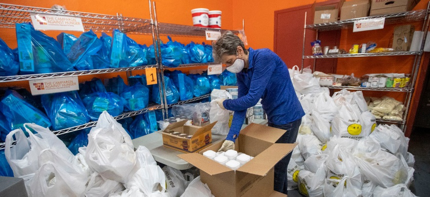 A volunteer prepares bags of groceries for delivery in Brooklyn. The pandemic has spurred tremendous need as well as a surge in volunteerism. Federal employees must ensure their activities remain within ethical boundaries, officials say.