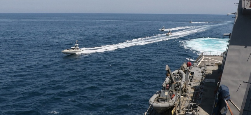 In this April 15 photo made available by U.S. Navy, Iranian Revolutionary Guard vessels sail close to U.S. military ships in the Persian Gulf near Kuwait.