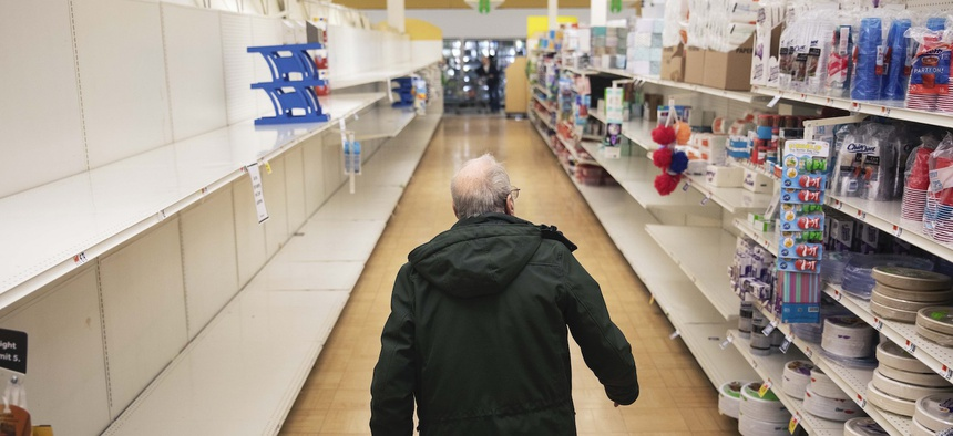 A shopper looks for toilet paper at a Stop & Shop supermarket during hours open daily only for seniors Thursday, March 19, 2020, in North Providence, R.I.
