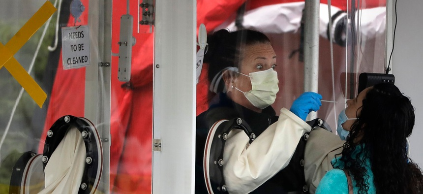 A medical worker, left, tests a person for the coronavirus from inside a booth on April 16 at MGH Chelsea HealthCare Center, in Chelsea, Mass.