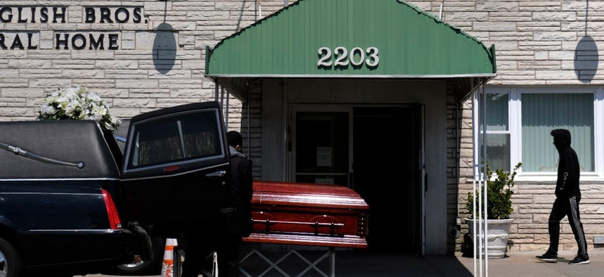 A pedestrian walks past the English Bros Funeral Home as a casket is unloaded in Brooklyn on April 19.