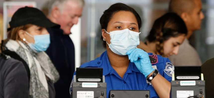 A TSA employee adjusts her face mask while screening passengers entering through a checkpoint at John F. Kennedy International Airport in New York in March.