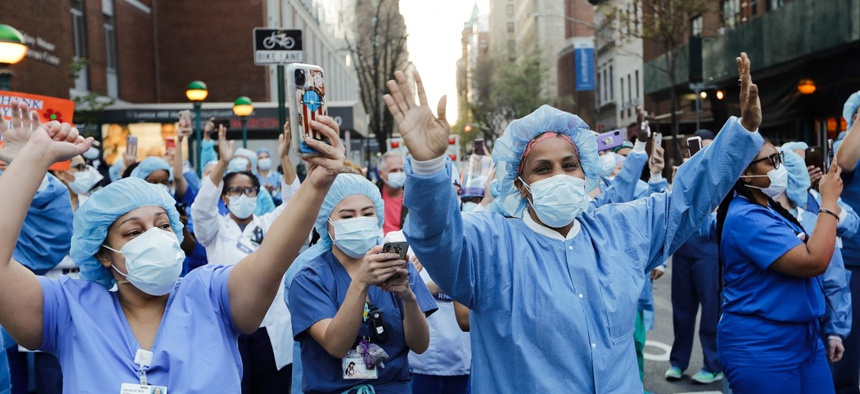 Nurses and medical workers react as police officers and pedestrians cheer them outside Lenox Hill Hospital Wednesday, April 15, 2020, in New York.
