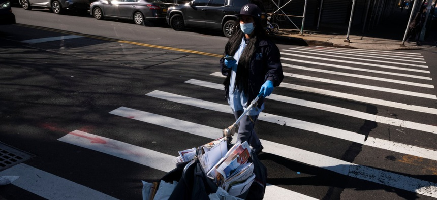 A postal worker wears a mask and gloves as she delivers the mail in Brooklyn in March