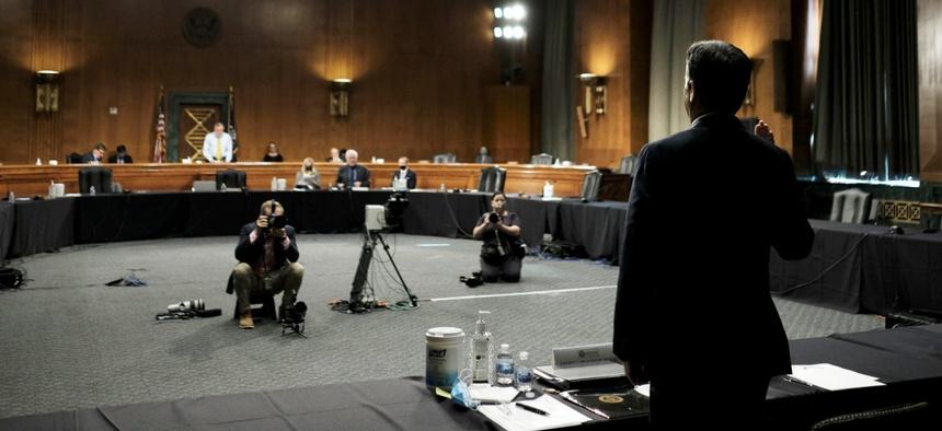 Rep. John Ratcliffe, R-Texas, right, is sworn in by Senate Intelligence Committee Chairman Sen. Richard Burr, R-N.C., standing left, before a Senate Intelligence Committee nomination hearing on May 5.