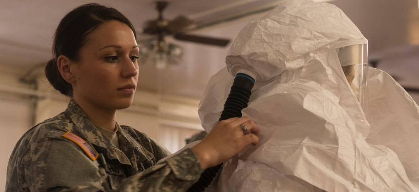 Kaiya Capuchino (left), United States Army Medical Research Institute of Infectious Diseases (USAMRIID) combat medic, helps a student don personal protective equipment during hazardous material training in 2014, at Tripler Army Medical Center in Haw