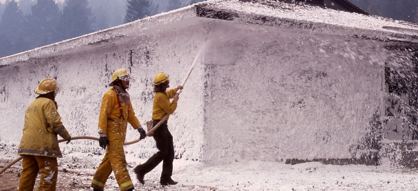 A firefighting crew foaming a dormitory at Mammoth Hot Springs during the 1988 Yellowstone fire. Firefighting foams are among the many substances that contain PFAS.