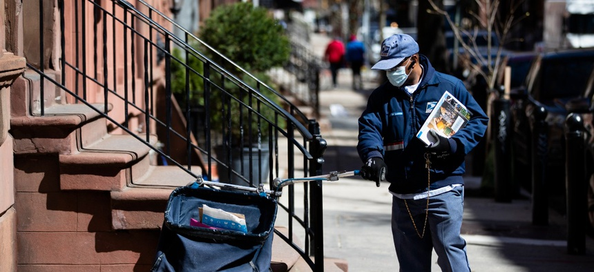A postal worker delivers mail in Philadelphia on April 2.