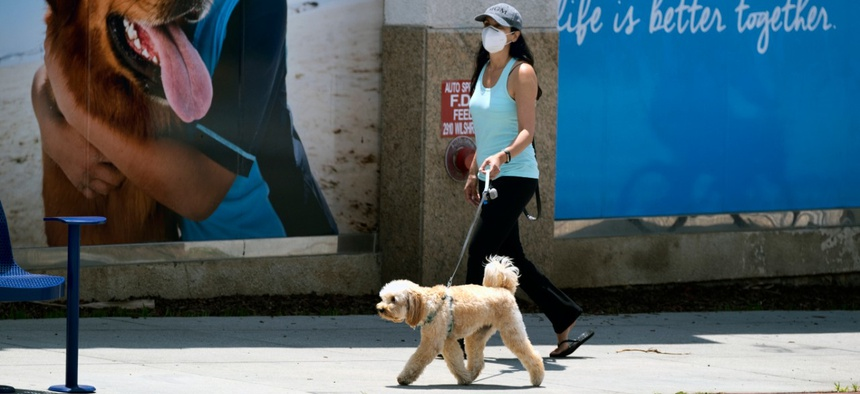 A woman wearing a protective mask for protection from the new coronavirus walks her dog in Santa Monica, Calif., on Saturday, May 9.