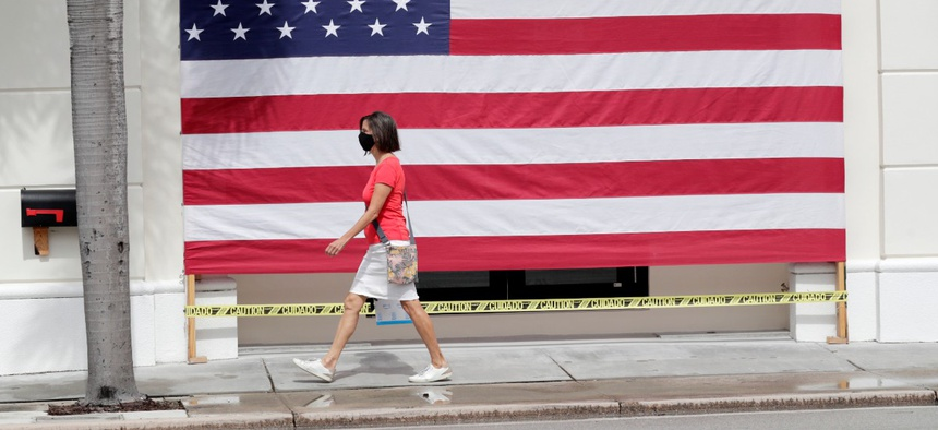 A woman wearing a protective face mask walks past an American flag in front of a closed business in Florida on Monday.