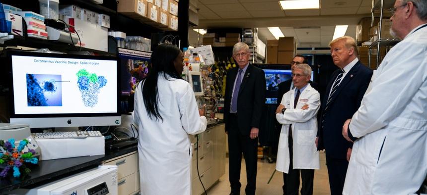 Dr. Kizzmekia Corbett, senior research fellow and scientific lead for coronavirus vaccines and immunopathogenesis team in the Viral Pathogenesis Laboratory, left, talks with President Trump as he tours the Viral Pathogenesis Laboratory at NIH in March.
