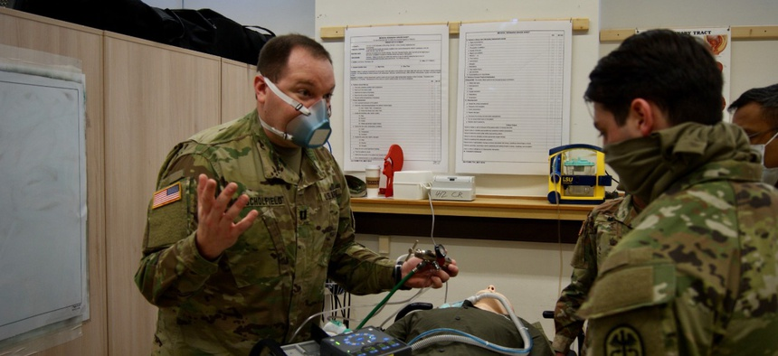 Army Capt. James Schofield, assigned to the 4th Squadron, 2d Cavalry Regiment, explains the differences between the types of respirators available for medical providers during training in Rose Barracks, Germany.
